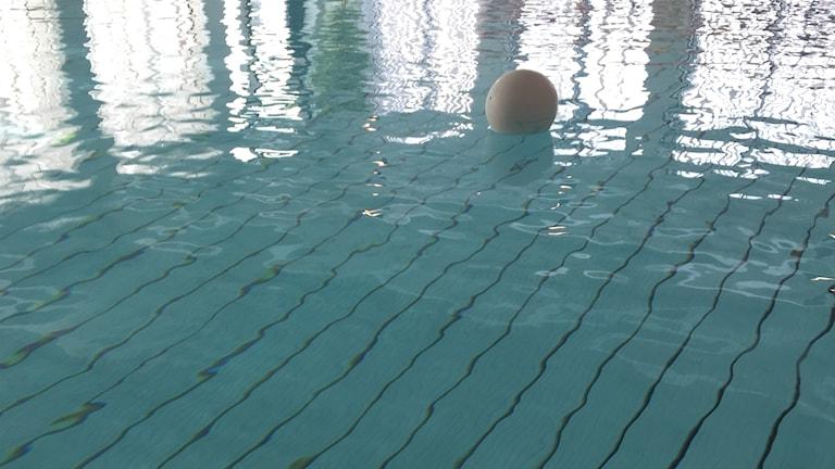 En vit boll ligger och flyter i en blå badbassäng.