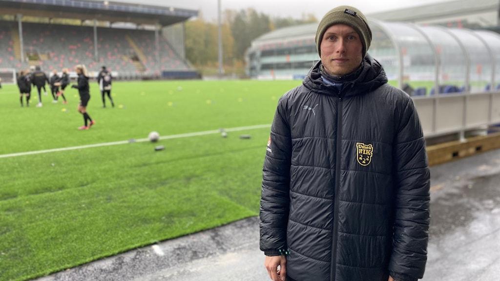Umeå IK:s tränare Samuel Fagerholm tittar in i kameran. Bakom honom är en fotbollsplan där damlaget tränar.