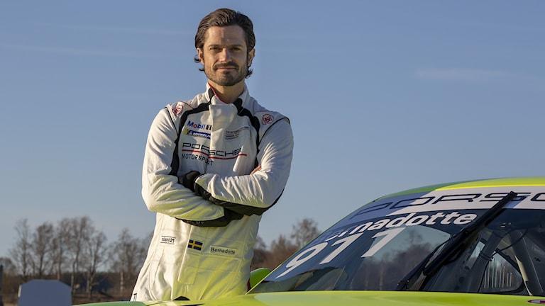Prins Carl Philip står med armarna i kors intill sin racingbil.