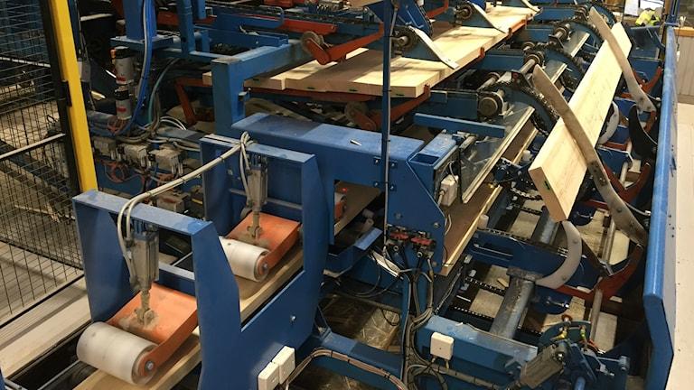 En blå industrirobot som sorterar upp och transporterar plankor på ett sågverk