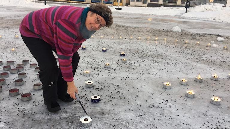 Elisabet Lindgren vid kvinnojouren i Lycksele tänder marschaller på torget.