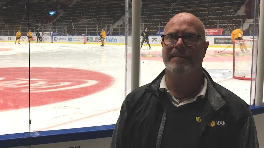 P4 Västerbottens hockeyexpert står vid rinken där Skellefteå AIK tränar i bakgrunden.