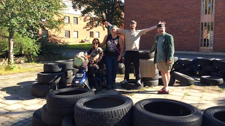 En grupp människor som står bland uppstaplade däck som så småningom ska bli en Biodom.