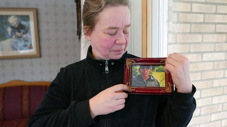 Gunilla med ett foto av sin make.