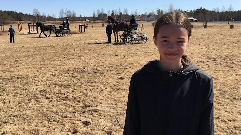 12 åriga Saga Pettersson står i solen med sportkörningshinder och tränande ekipage i bakgrunden, en vår då det torra fjolårsgräset täcker fältet.