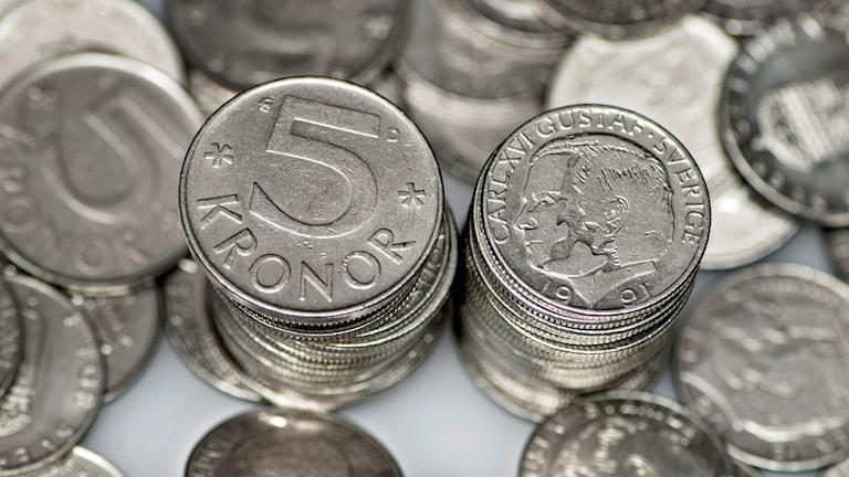 Gamla mynt, 1-konor och 5-kronor, i högar