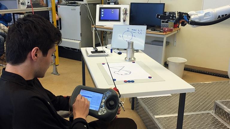 Anton Jonsson programerar en industrirobot