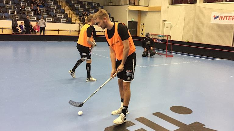 Alexander Rönnlund, till vardags IBK Dalen i dag laget Penguins, står på planen med boll och klubba.