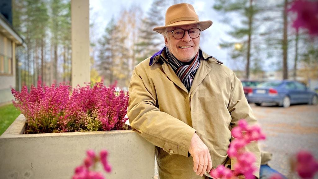 Per-Martin Jonasson, regional samordnare för riksinsamlingen till Världens barn. Står utanför sveriges radio bland rosa blommor. har på sig beige trenchcoat och en beige hatt.