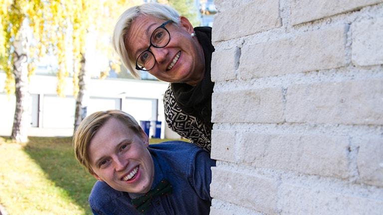 Humorduon Agneta Stefansson och Erik Moberg tittar fram bakom en husknut