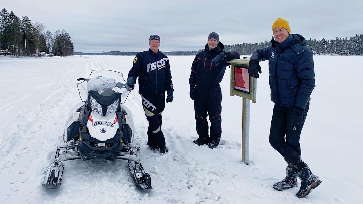 Roberth Forsgren, Jukka Linna, Robert Lindberg som drar längdskidspåret på Nydalasjön i Umeå står vid skotern ute på isen.
