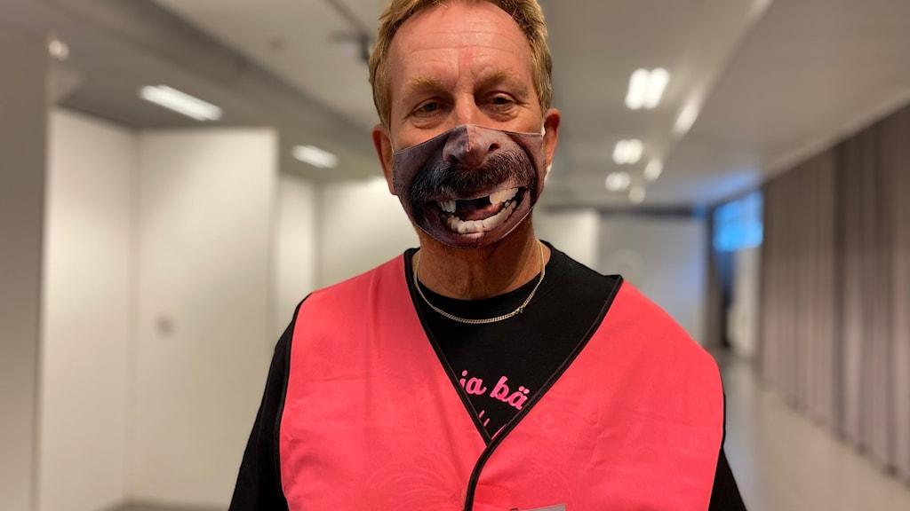 Dick Selberg i rosa varselväst och munskydd i tyg på Nolia.
