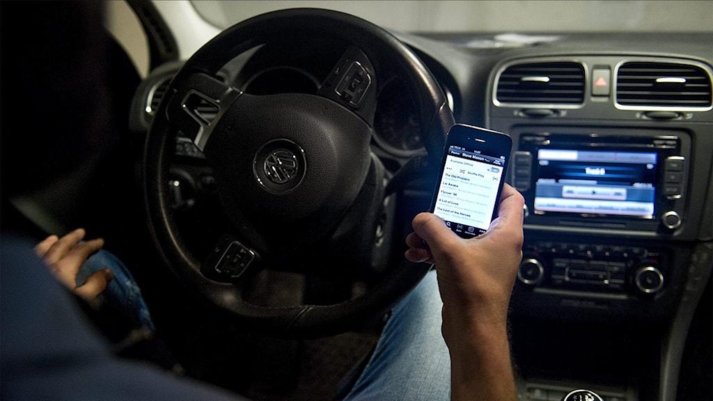 Man i bil sitter och styr musik i bilstereon från sin telefon.