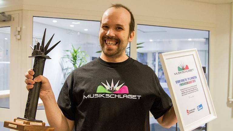 Kenneth Heino vinnare av Musikschlaget 2017 håller upp trofén och ett diplom