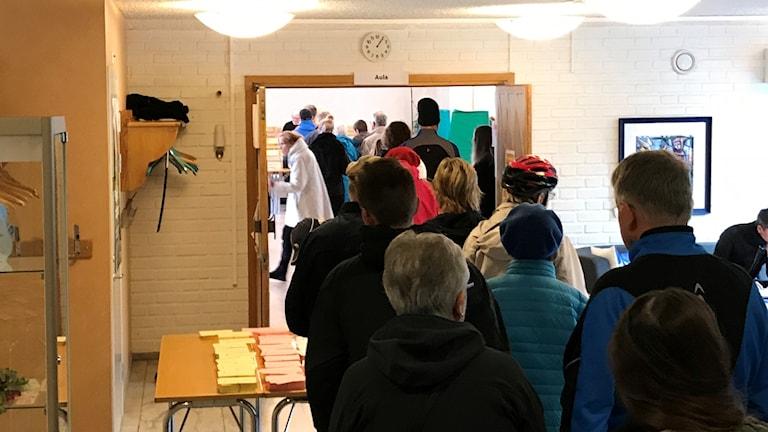 Människor i ytterkläder köar för att komma in i en vallokal. Vid ena sidan syns ett bord med valsedlar.