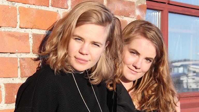 Anna Brodin och Miranda Larsson i solen vid tegelvägg