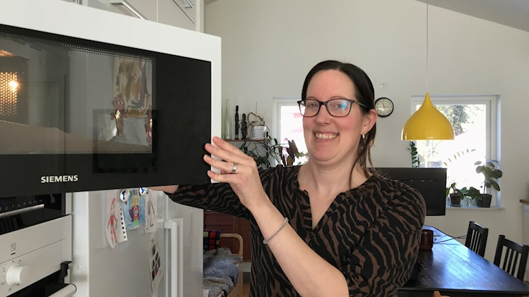 Jenny Ask lägger in sin lunchlåda i mikrovågsugnen hemma i köket.
