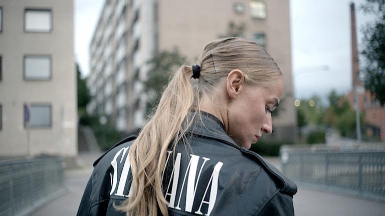 Silvana Imam i svart skinnjacka med ryggen mot kameran, ur dokumentärfilmen Silvana - väck mig när ni vaknat.