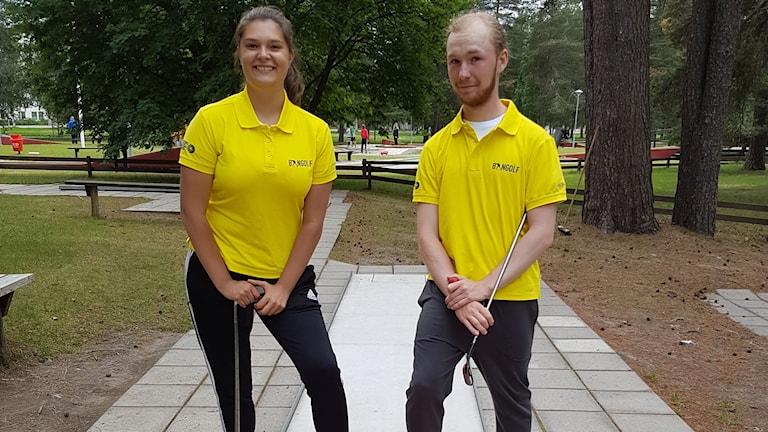 En tjej och en kille i gula tröjor och med minigolfklubbor i händerna.