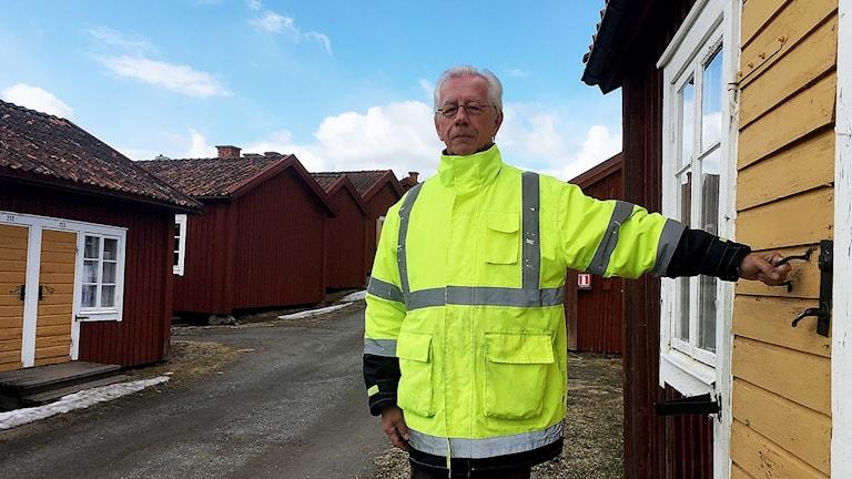 Johnny Karlsson, ordförande i Lövånger Kyrkstad AB står bredvid de gamla kyrkstugorna