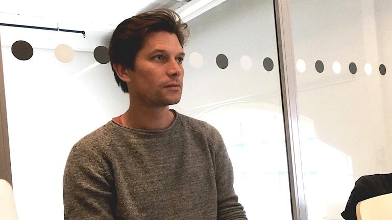 Joacim Rocklöv sitter vid ett bord med en dator framför sig
