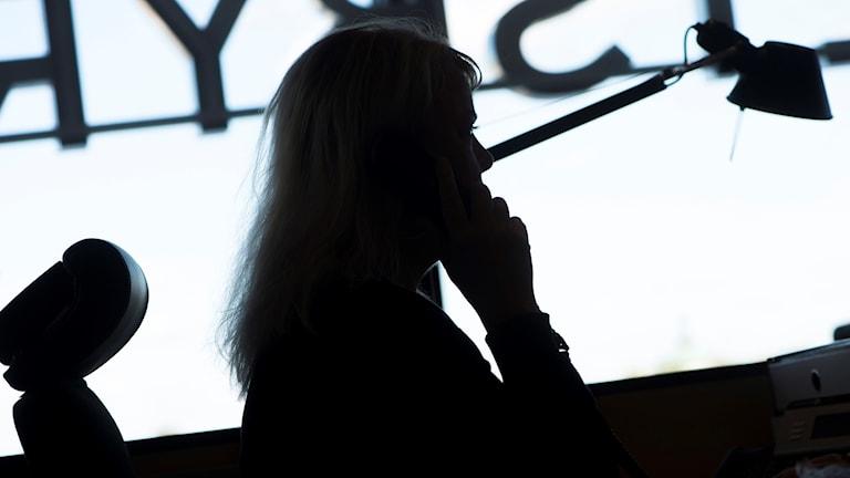 Siluetten av en kvinna som sitter på ett kontor och pratar i telefon
