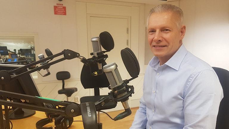 gråhårig man i ljusblå skjorta, sitter framför en mikrofon i en radiostudio och ler mot kameran.