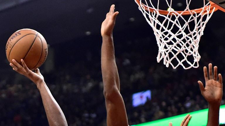 Basketboll mot korg med två försvarande händer.