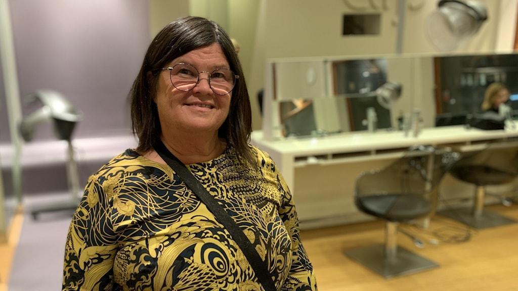 En kvinnlig frisör står i sin salong.