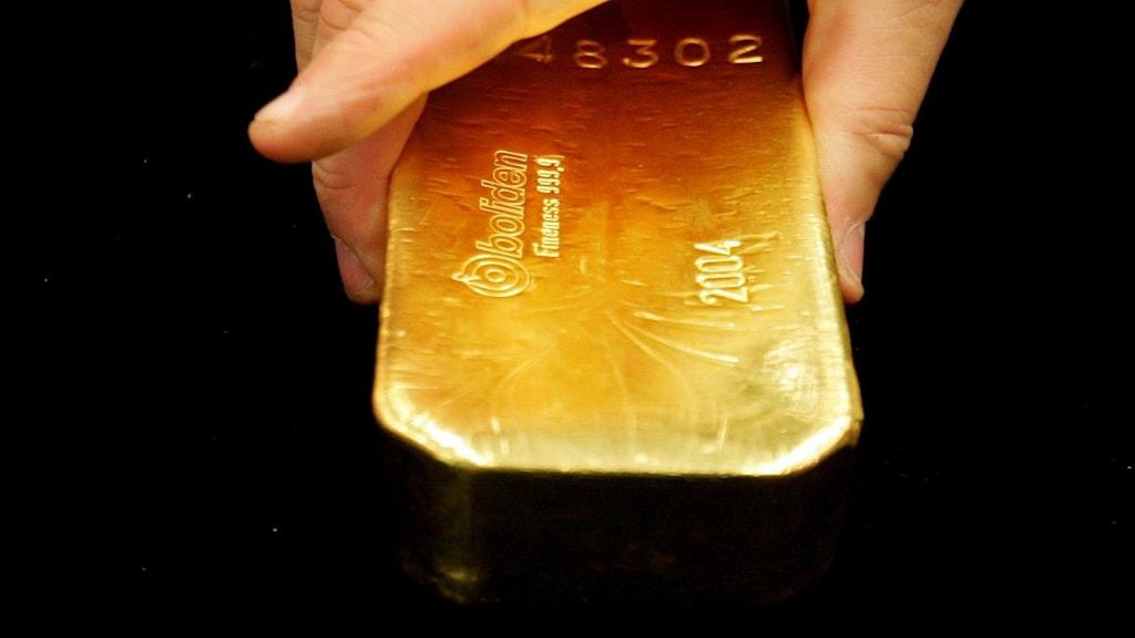 Besökare på seniormässan på annexet i Globen försöker lyfta den 12,5 kg tunga guldtackan från Boliden.