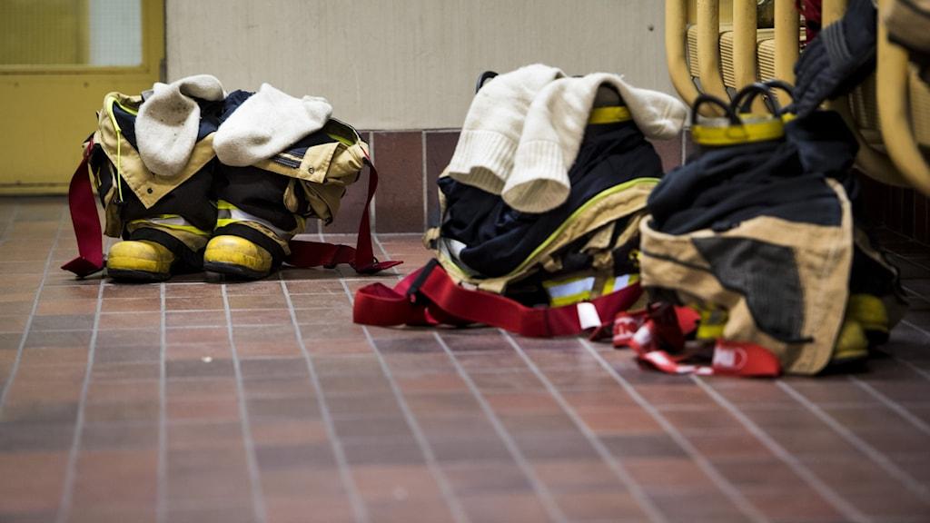 Brandstation med brandmäns skyddskläder förberedda för uttryckning.