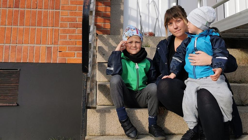 En mamma sitter med sina två barn på skoltrappa. Pojkarna är sex och två år gamla.