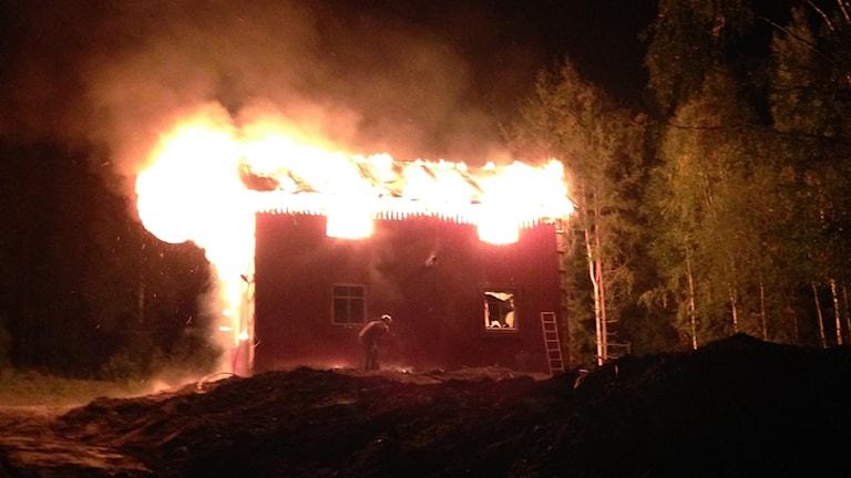 Ett rött hus brinner, helt övertänt.