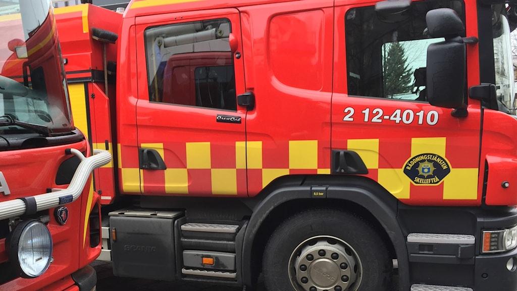 Hytten av en brandbil från sidan och en andra brandbil som skymtar