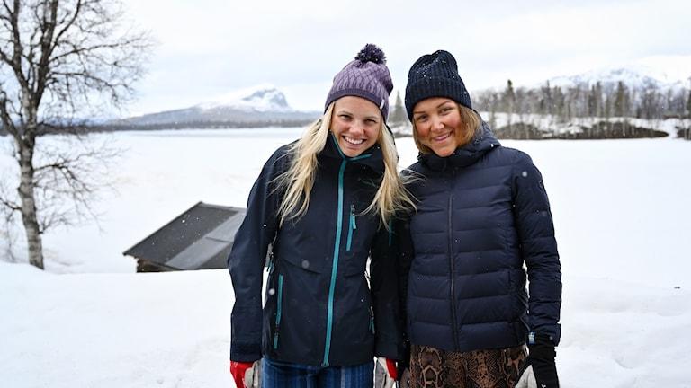 Skidåkarna Emma Ribom och Moa Lundgren på plats i Saxnäs, snötäckta fjälltoppar syns i bakgrunden.