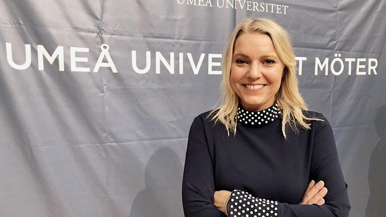 Carina Bergfeldt framför ett skynke med texten Umeå universitet