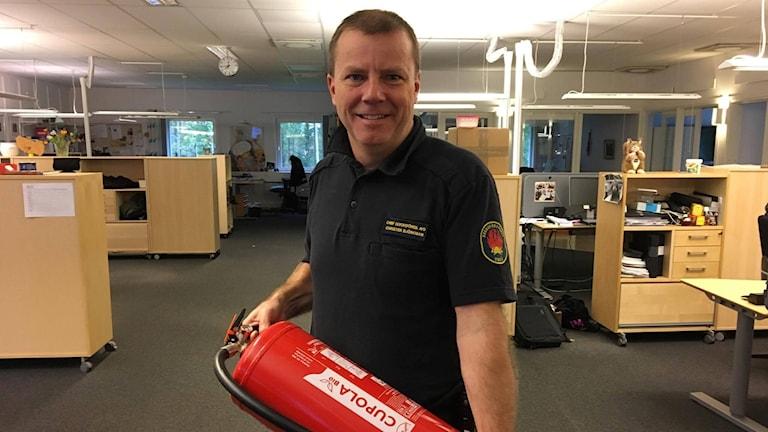 Christer Björkman, brandingenjör på Umeå brandförsvar med en brandsläckare