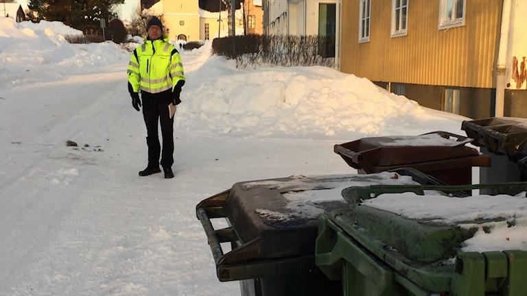 Tomas Nilsson, Skellefteå kommun, står på en uppfart med framskottade soptunnor.