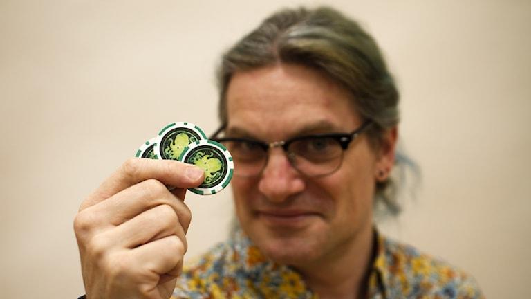 Spelrecensenten Jonas Danielsson håller fram markörer från ett spel