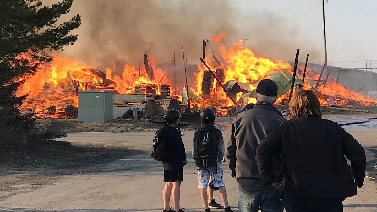 Människor står samlade och tittar på branden.