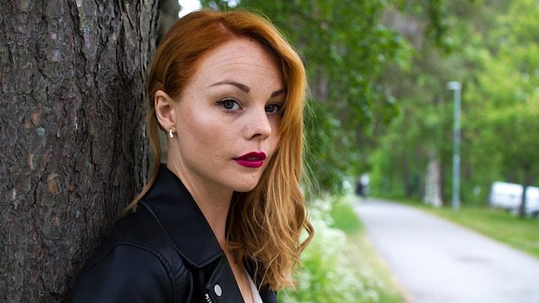 Anna Nilsson tävlar i P4 Nästa som To Carry Anne, här står hon mot ett träd bredvid en cykelväg