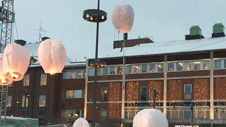 Svävande lyktor lämnar Rådhustorget i Umeå.