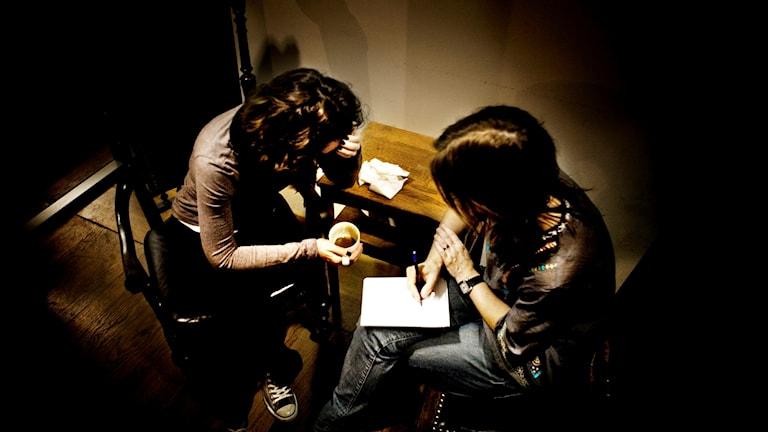 Två anonyma personer sitter på varsin stol i ett mörklagt rum
