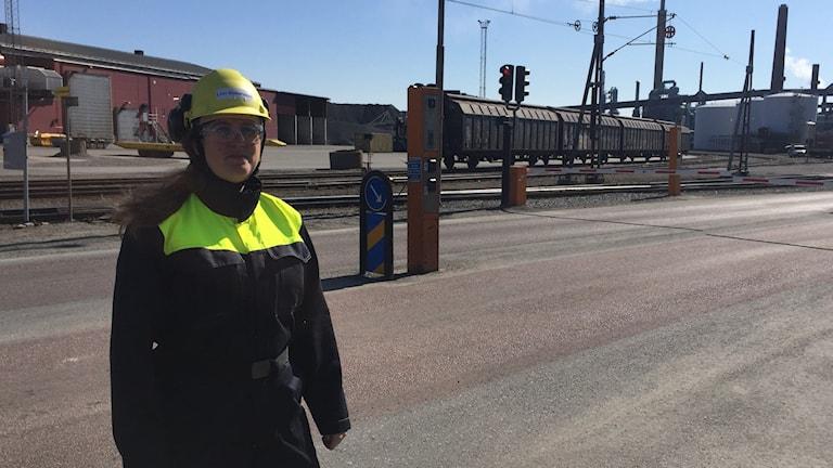 I vårsolen står Linn Andersson vid grinden till det stora industriområdet som utgör Bolidens Anrikningsverk i Skelleftehamn, bakom henne ses industrins skorstenar och ett par vagnar till ett godståg.