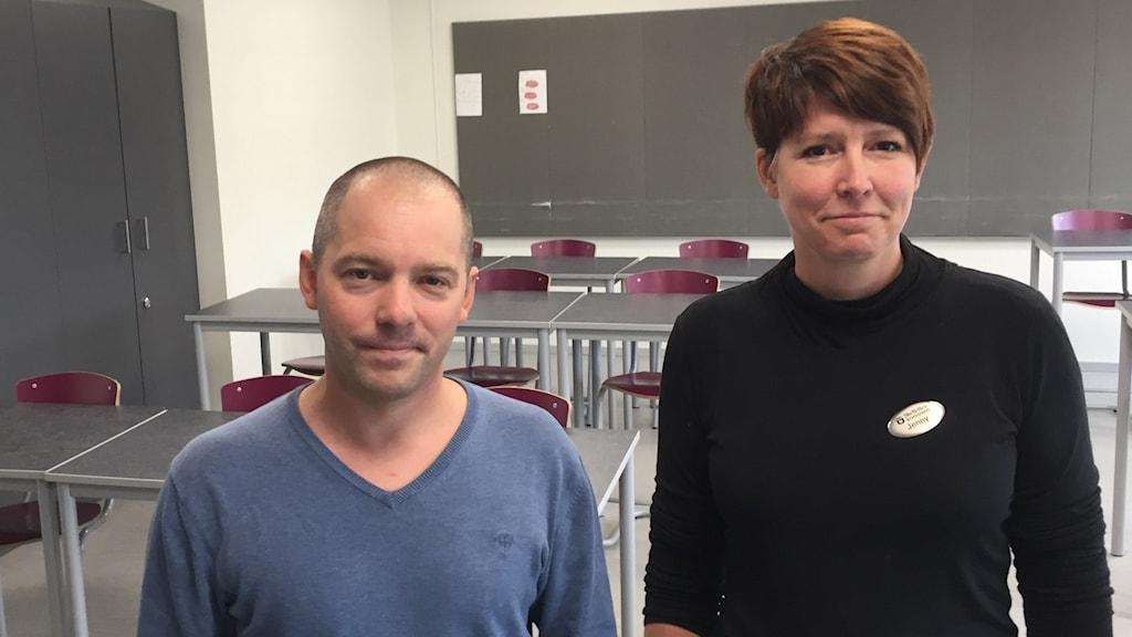 I ett klassrum framför grå bänkar och lila stolar står Andreas Eriksson svenskalärare Bolidenskolan och Jenny Eriksson rektor Bolidenskolan.