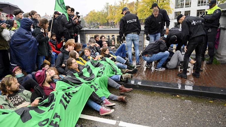 Demonstranter sitter på gatan och håller i banderoller.