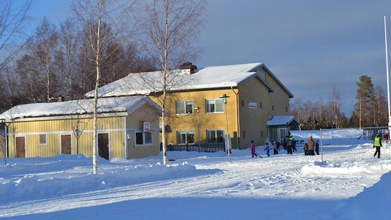 Skola med snö på taket och barn som leker utanför.