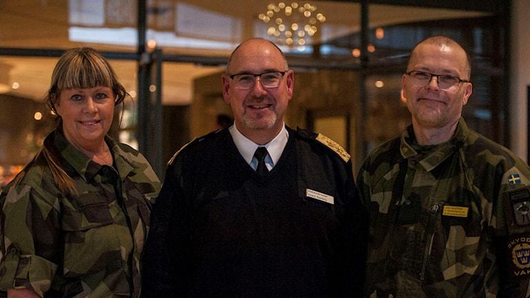 En kvinna och två män, klädda i militära kläder.