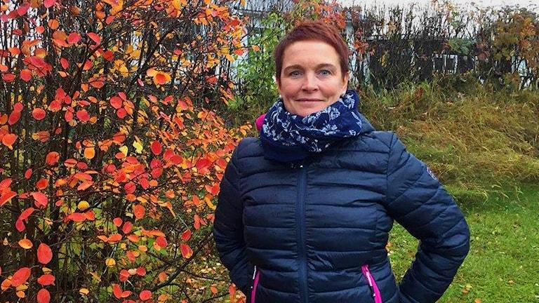 Magdalén Lindström ordförande för Skellefteås reumatikerförening bredvid ett träd med röda löv