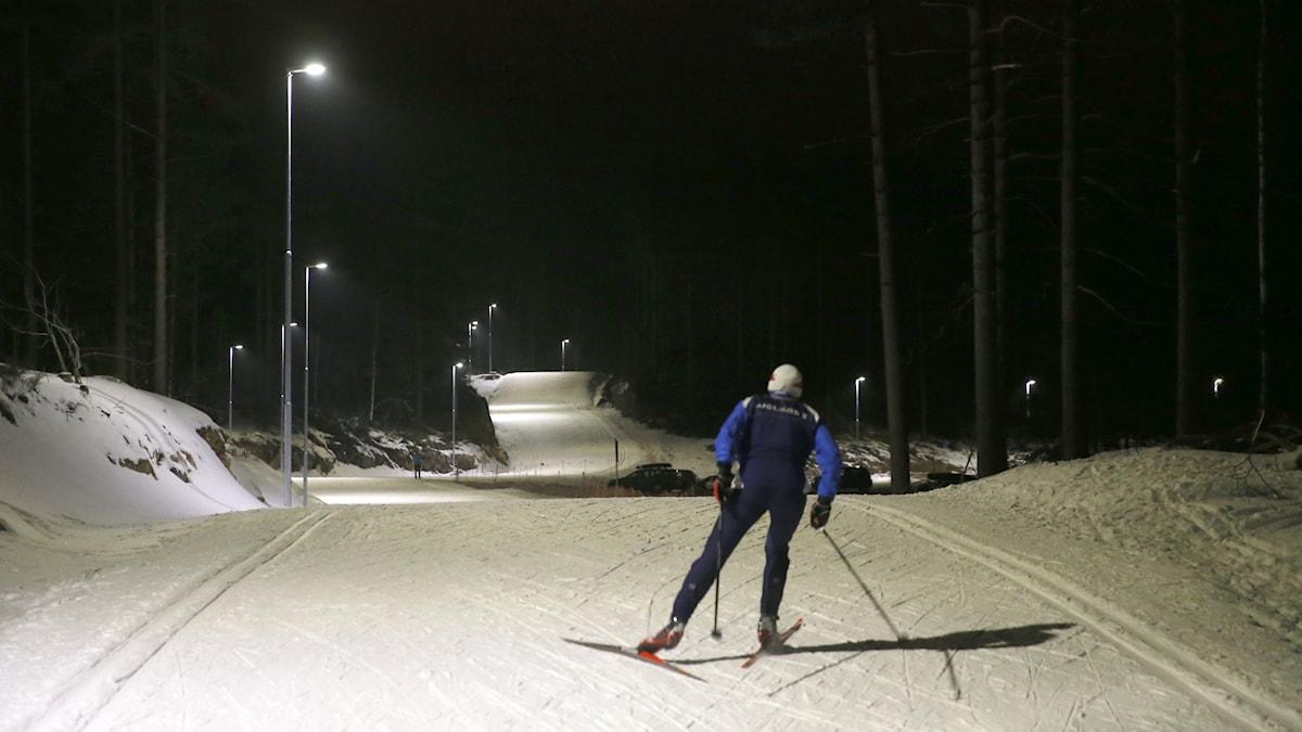 En skidåkare som åker på ett elljusspår.